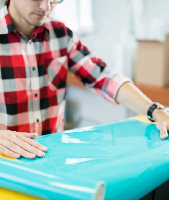 Close-up of busy concentrated young man in checkered shirt touching glossy paper while checking quality in typography